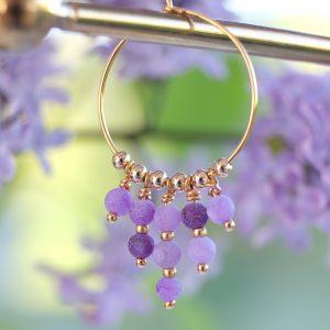 Billedet viser lilla Syren farvede øreringe i guld hoops